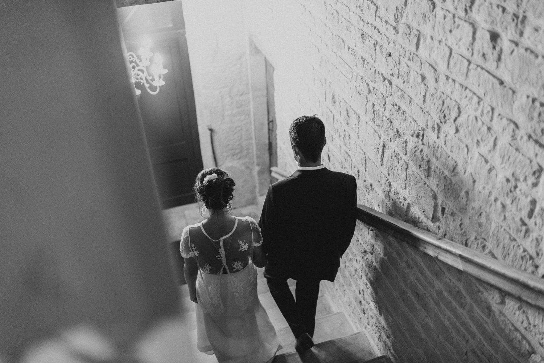 Couple de mariés qui descend les escaliers, photo en noir et blanc